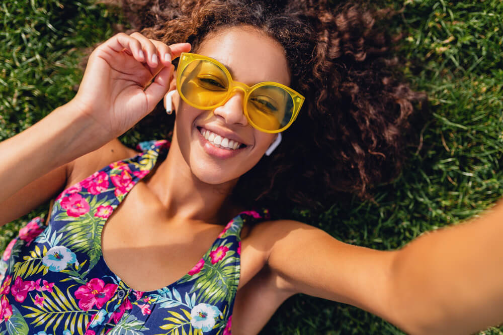 young stylish black woman listening music wireless earphones having fun lying grass park taking selfie photo phone camera summer fashion style colorful hipster outfit view from1 - Sora Solutions Services